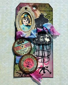 CREATIVITY IS CONTAGIOUS  Layered tag using inks, masks and stamps to achieve the background using Tim Holtz' summer distress ink colors. The tag is then embellished with Tim Holtz' dress form and thread labels stamps from Haberdashery. The spool labels are colored using distress inks and a water brush. They are mounted on distressed chipboard made to look like a wooden spool top. The frame is Tim's book plate die cut on Grungeboard, painted and crackled. The girl is from Girls Rule.