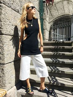 Pernille Teisbaek wears a black cutout tunic, white culottes, slide sandals, Ray-Ban sunglasses, and gold jewelry