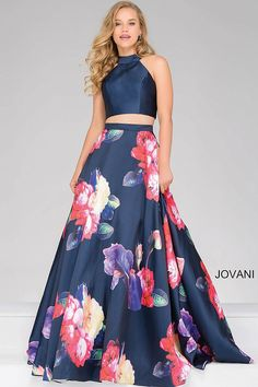 Stunning navy floor length two piece sleeveless prom dress features high neckline and a floral print a-line skirt.