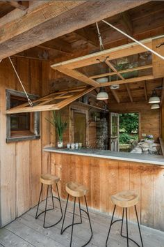 This upstate New York lakefront home's outdoor entertaining and kitchen space features a pulley system, so that the windows can be raised, opening the space up to the great outdoors. See more photos of this home at Pearson Design Group.