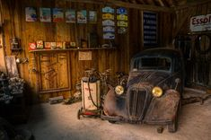 Photo of a car repair shop from the 1940s or 1950s. It's on display in a museum in France.