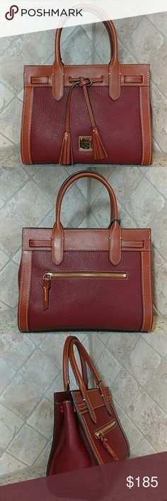 """🎉HP 3/29🎉 Dooney & Bourke Pebble Leather Satchel 'Ariel' softly structured satchel in rich pebbled leather w/smooth contrast leather trim. Color:  Wine   Exterior features beautiful red fabric lining, 1 zip pocket, 3 slip pockets, and key hook. Exterior features one zip pocket, magnetic snap closure, twin tassel detail.  Goldtone hardware w/protective metal feet at bottom of bag.  5""""L drop double handles.  Dust bag included. Dooney & Bourke Bags Satchels"""