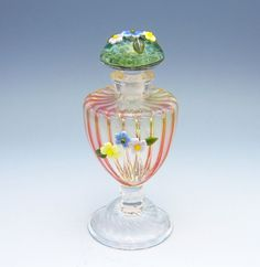 Pink Urn Perfume Bottle by Chris Pantos. Pink ribbed perfume bottle with blown foot and floral detailing. The stopper has floral detailing on a ground glass base. This bottle is ground.