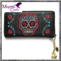 PURPLE SUGAR SKULL FLORAL WALLET PURSE by BANNED. The purple skull wallet is wonderful made from 100% black PVC with a purple skull and flower appliques to the front for effect. The inner compartments easily carry bank and credit cards as well as bank notes. There is a zipped inner section to keep loose change.