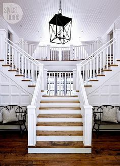 Grand Foyer Staircase. Coastal Foyer Staircase designed by Muskoka Living Interiors. #MuskokaLivingInteriors #Staircase #Foyer