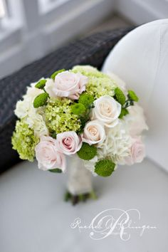 Pretty pink, blush, and ivory roses mixed with green hydrangea and button chrysanthemums in a round bridal bouquet.
