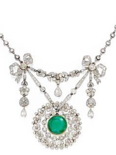 A Belle Époque platinum, gold, emerald and diamond pendant necklace. The garland-style pendant gathered at the sides with bows, centring a round emerald, accented by pear-shaped, old mine, old European and rose-cut diamonds, suspended from a necklace of later addition, set with round diamonds, circa 1910. #BelleEpoque #pendant #necklace