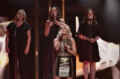 Carrie Underwood Photos - (L-R) Liz Rose, Hillary Lindsey, Carrie Underwood and Lorie McKnna perform on stage at CMT Artists of the Year 2016 on October 19, 2016 in Nashville, Tennessee. - CMT Artist of the Year - Show
