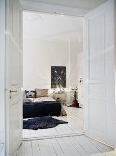 Swedish home in white. grey and brown. Drinks trolley as a bedside table....Stadshem