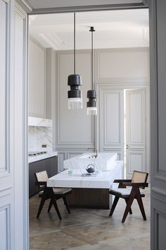 In the kitchen, all technical elements are hidden behind calacatta marble partitions. Bronze 'Fingi' suspension lighting by Eric Schmitt (Eric Schmitt). Office armchairs by Pierre Jeanneret (Galerie 54).  http://www.yatzer.com/joseph-dirand-saint-germain-paris // Photo © Adrien Dirand / AD France n° 119, September/October 2013.