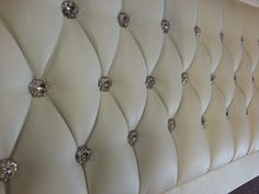Faux upholstered headboard with crystals.