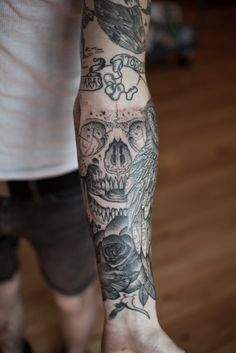 Arm tattoo. Skull, Rose and Feathers.