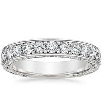 This elegant vintage inspired ring is engraved with a beautiful scroll pattern on the top and sides of the band. A row of shimmering pavé diamonds flows halfway down the shank enhance the glamour of this piece.
