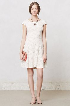 Simple short white stretch lace dress with and almost boat neck and cap sleeves... above the knee length and very flattering.  Love this for contrast against a busy background for a rustic engagement photography shoot... This is the Dayflower Lace Dress from Anthropologie...