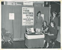 """This photograph depicts some unknown women at an American Cancer Society booth.  As you can see, it's from the Lake County Unit, and it's labeled """"Food Show Gary Armory, June, 1949"""".  From my personal collection."""