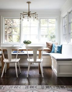 An Arteriors Sabine Brass Chandelier hangs over a light wood dining table seating white wood dining chairs and a white l-shaped wainscoted dining bench topped with a gray seat cushion and blue and brown pillows placed beneath windows.