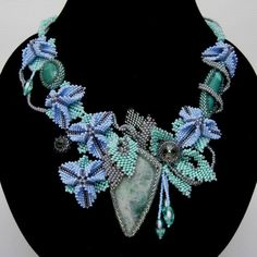 Beadwork by Nadya Gerber this is beautiful!  the green leaves look like st petersburg stitch but what are the blue ones?