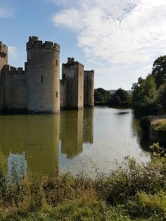 A view of the beautiful Bodiam Castle in East Sussex against blue sky, the medieval towers reflected in the moat - my review and why it's great to visit Bodiam Castle with kids