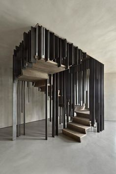 Concrete stair case and surroundings with suspended metal divider for stairs.