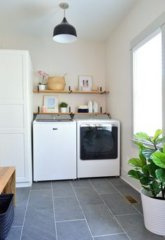 Top loading washer. Laundry room with slate floors black light fixture open wood shelves