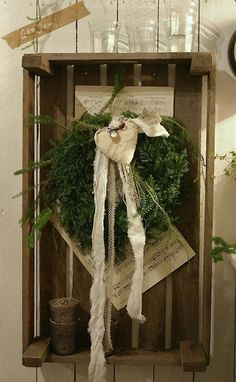 evergreen wreath with lace and cotton in wooden crate