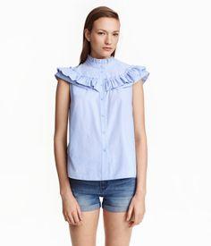 Lichtblauw/stippen. Een blouse van geweven katoen met een knoopsluiting voor. De blouse heeft een halsboordje met een opstaand volantrandje en volants langs