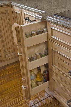 Custom Pullout Storage--Narrow panels flanking the cooktop pull out to reveal clever custom storage. This pullout accommodates both small spice jars and tall cooking oils. Conveniently close to the cooktop, the pullout makes it easier to grab the right herb while sauteing dinner. A matching pullout on the opposite side of the stove keeps linens close at hand.