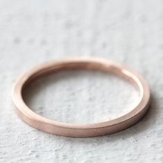 "Solid gold simple flat band. This solid 14k gold women's wedding ring or everyday ring comes in 14k rose or yellow gold. It is the perfect little band to wear everyday. The band can be finished with a matte/brush finish (as shown on the rose gold rings) and polished (as shown on the yellow gold rings). Please leave the finish you would like in the ""notes"" box at checkout. The ring measures 1.5mm x 1.5mm, so it is perfectly square to create a unique and interesting ring. My ..."
