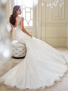 Sophia Tolli | Style No. › Y21438 | Wedding Dresses 2014 Collection – Live out a romantic fantasy with Luise, a sparkling mermaid gown in misty tulle. Decadent embroidery and crystal hand-beading adorn the subtly scooped neckline, sheer cap sleeves and figure-flattering bodice with a dramatic dropped waist. Embroidery and beading cascade down the skirt and chapel length train. A back corset is [...]