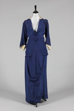 A sapphire blue moire silk walking suit, circa 1914, the jacket with pointed rear hem, rouleaux frogging fasteners and floral adornments, matching hobble skirt, bust 81cm, 32in;
