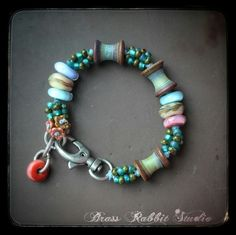 """Lampwork spools by Leah Deeb, seed beads, Lampwork charm and rounds by Ellen Dooley, silver lobster clasp, fits a 6""""-7"""" wrist."""