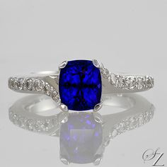 Delicate and feminine, this pretty ring is simply stunning. The rich, velvety Tanzanite set with glittering fine white Diamonds that twist and trail gracefully down the band is absolutely captivating.