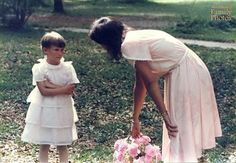 """""""This photo was captured by my uncle at my mom's wedding to my step-father, when I was five. I was supposed to be flower girl and here is my mom trying to convince me to carry out my duties. I was unhappy about my haircut at the time being so bad and boyishly short. I was also unhappy about wearing a dress. I have never been very girly and can count the number of times I've worn a dress on one hand."""""""