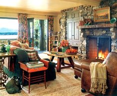 Family Room with lake view. I've never seen stone surrounding a built-in. Warm wood and leather, stone, floral drapes, lots of pillows, pops of orange/coral. Fabulous!