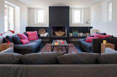 cheminée noir, sol béton noir ,mur blanc, canapé anthracite avec coussins colorés