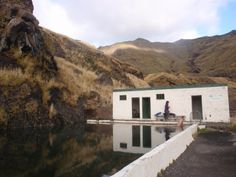 """Seljavallalaug is a small pool built into the mountainside by the local Youth Club in the 1920s, fed by piped-in hot spring water and one rogue cliffside trickle. It's at the instep of the Eyjafjoll Mountains, a fifteen-minute walk (over rocky streams and under basalt turrets) off the end of road 242."""