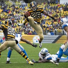 The Steelers' Le'Veon Bell leaps over top of the Lions' Willie Young in the second quarter for a first down at Heinz Field.