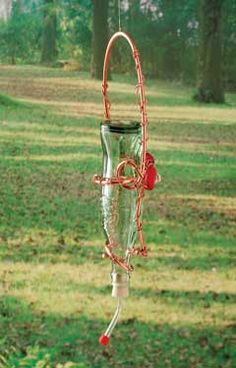 Make this recycled DIY hummingbird feeder for just a few bucks by using a recycled bottle and inexpensive decorative accents. Homemade Hummingbird Feeder, Glass Hummingbird Feeders, Humming Bird Feeders, Humming Birds, Wine Bottle Crafts, Bottle Art, Diy Bottle, Mini Malteser, Homemade Bird Houses