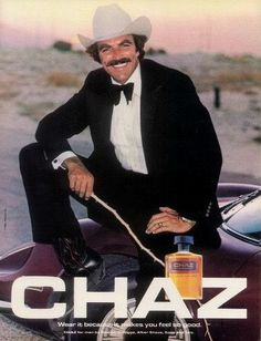 """An original 1981 advertisement for Chaz Cologne. Featuring Tom Selleck dressed as a cowboy. A clean white cowboy hat, slick formal suit, and a pair of cowboy boots. """"Wear it because it makes you feel"""