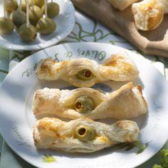 Blätterteigscheiben bei Zimmertemperatur auftauen lassen. Oliven auf einem Sieb abtropfen lassen. Eigelb mit Sahne verquirlen. Backblech mit...