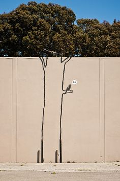 Banksy singing bird mural in a parking lot at Mission and Erie streets. 10+ artists later added tree-themed works to the wall.