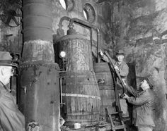 Dismantling a 300 gallon moonshine still found in a raid near Crestwood are Elmer C. Davis and Mark Holmes, agents of the Federal Alcohol Tax Unit. At left is a steam boiler, and in center is the actual still. Mar 4 1951. Photo by James N. Keen, THE COURIER-JOURNAL