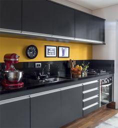 Um frontão de granito são gabriel, de 30 cm de altura, mesmo material da bancada da pia, protege a parede. A faixa de pintura na cor Amarelo Ômega* (Coral) faz o link visual com a estante.