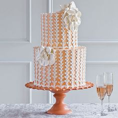 Peach and White Wedding Cake | This simple, two-tiered confection is covered with blush-colored buttercream and embellished with a bold budding patterm. The large white buttercream flowers give this cake a romantic look and the scalloped cake stand mimics the vertical piping.