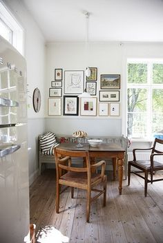Small Square Wooden Dining Table in a Corner with a bench seat and two chairs; gallery wall of pictures; beaded board wainscot on walls; wide plank wood flooring; vintage pendant light fixture; and, large windows