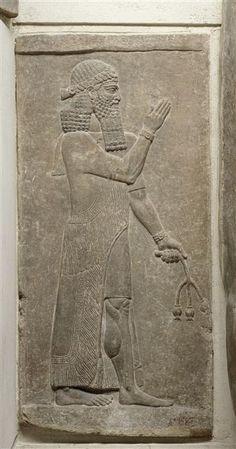 Personnage tenant une fleur de pavot  - Assyrie | Site officiel du musée du Louvre