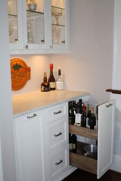 Roll out liquor cabinet on side of other cabinets or wine fridge
