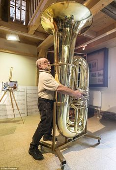Balancing act: Musical instrument craftsman Hartmut Geilert demonstrates how to play the world's largest functional tuba at the Musikinstrumenten-Museum in Germany