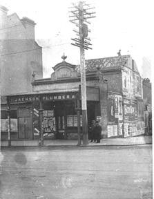 Jackson Plumbers at the corner of Bourke and William Streets in Woolloomooloo (year unknown). Pole Bear, Williams Street, Wooden Poles, Historical Photos, North West, Big Ben, Sydney, Jackson, Corner