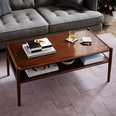 NEW! The Adrien Coffee Table's rich rosewood-inspired finish and simple profile make it a living room classic. Stow books and remotes on its wide open shelf.